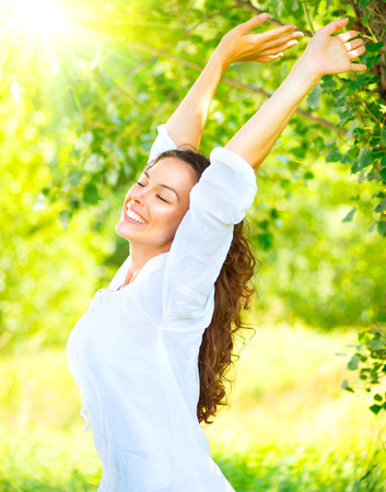 Photo pour Beautiful young woman enjoying nature outdoor. Happy and smiling brunette girl with healthy smile relaxing in the summer park - image libre de droit