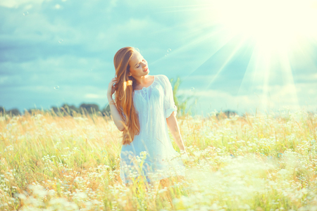 Foto de Beauty girl outdoors enjoying nature. Beautiful teenage model girl with healthy long hair in white dress standing on the summer field - Imagen libre de derechos