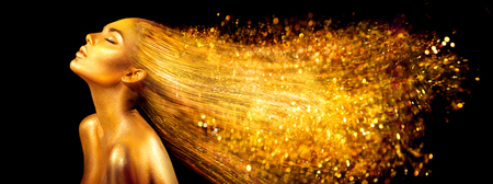 Foto de Fashion model woman in golden bright sparkles. Girl with golden skin and hair portrait closeup. Holiday glamour shiny professional makeup on black - Imagen libre de derechos