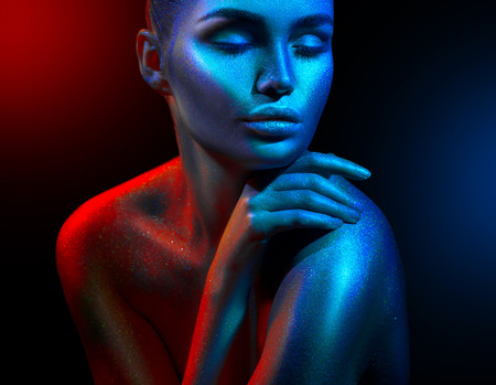 Photo pour Fashion model woman in colorful bright sparkles and neon lights posing in studio, portrait of beautiful sexy girl. Art design colorful vivid makeup - image libre de droit