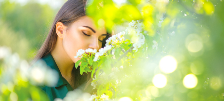 Foto de Beauty young woman enjoying nature in spring apple orchard, Happy beautiful girl in a garden with blooming fruit trees - Imagen libre de derechos