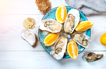 Foto de Fresh oysters close-up on blue plate, served table with oysters, lemon and champagne in restaurant. Gourmet food. Tabletop view - Imagen libre de derechos