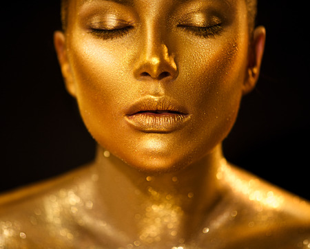 Photo for Golden skin woman face. Fashion art portrait closeup. Model girl with holiday golden glamour shiny professional makeup. Gold jewelry, accessories - Royalty Free Image