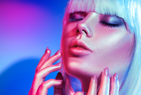 Photo pour Fashion model woman in colorful bright sparkles and neon lights posing in studio, portrait of beautiful girl, trendy glowing make-up - image libre de droit