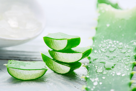 Photo for Aloe Vera gel closeup on white wooden background. Organic sliced aloevera leaf and gel, natural organic cosmetic ingredients for sensitive skin, alternative medicine. Skincare concept - Royalty Free Image