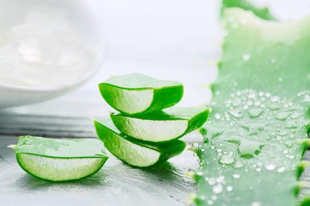 Foto de Aloe Vera gel closeup on white wooden background. Organic sliced aloevera leaf and gel, natural organic cosmetic ingredients for sensitive skin, alternative medicine. Skincare concept - Imagen libre de derechos