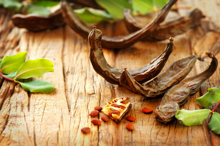 Photo for Carob. Healthy organic sweet carob pods with seeds and leaves on a wooden table. Healthy eating, food background - Royalty Free Image