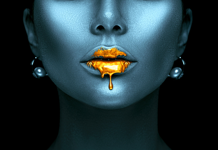 Photo for Gold paint drips from the sexy lips, golden liquid drops on beautiful model girl's mouth, creative abstract dark blue skin makeup. Beauty woman face - Royalty Free Image