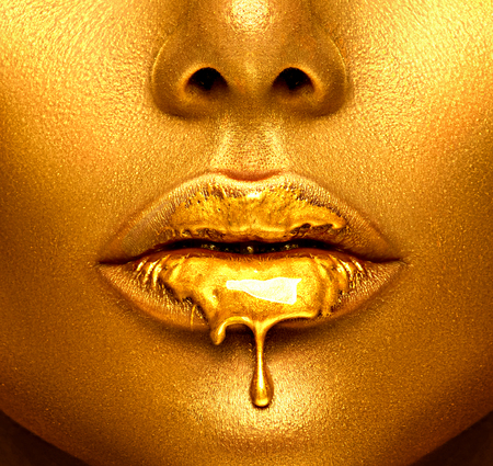 Foto de Gold paint drips from the sexy lips, golden liquid drops on beautiful model girl's mouth, creative abstract makeup. Beauty woman face - Imagen libre de derechos