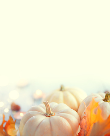 Foto de Thanksgiving background. Holiday scene. Wooden table, decorated with pumpkins, autumn leaves and candles. Vertical image - Imagen libre de derechos
