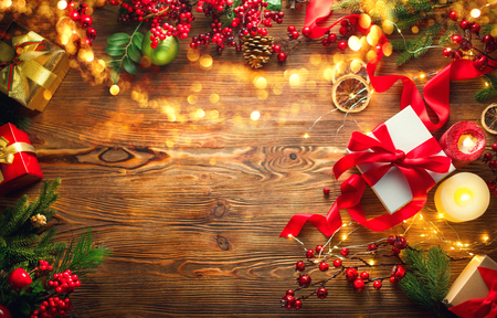 Photo pour Christmas scene. Colorful wrapped gift boxes, beautiful Xmas and New Year backdrop with gift boxes, baubles, candles and lighting garland over wooden table background. Top view, flatlay - image libre de droit