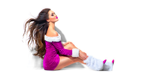 Photo for Sexy Santa. Beauty Christmas fashion model girl with blowing long curly hair. Brunette young woman wearing purple party costume - Royalty Free Image