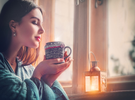 Foto de Beautiful brunette girl drinking coffee at home, looking out the window. - Imagen libre de derechos