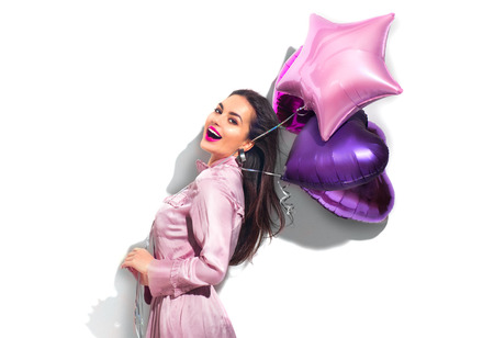 Foto de Beauty fashion model party girl with heart shaped air balloons having fun. Birthday party, Valentines Day. Beautiful young brunette woman over white background - Imagen libre de derechos