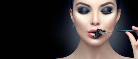 Foto de Beautiful fashion model woman eating black caviar. Beauty girl with caviar on her lips isolated on black background - Imagen libre de derechos