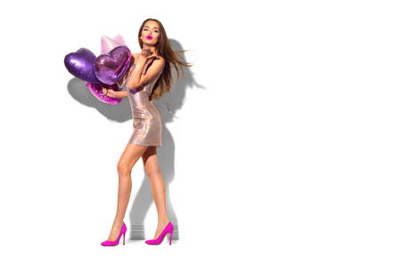 Photo for Beauty fashion model party girl with heart shaped air balloons posing. Beautiful young brunette woman full length portrait isolated on white - Royalty Free Image