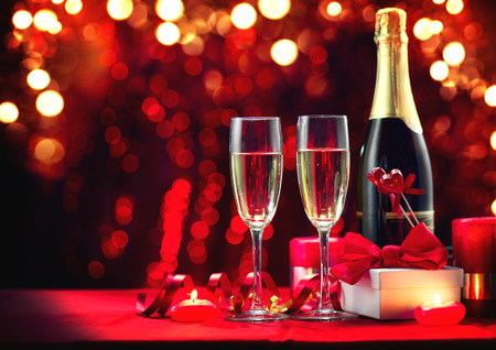 Foto de Valentine's Day romantic dinner. Champagne, candles and gift box over holiday red background. Wedding celebrating. Birthday party - Imagen libre de derechos