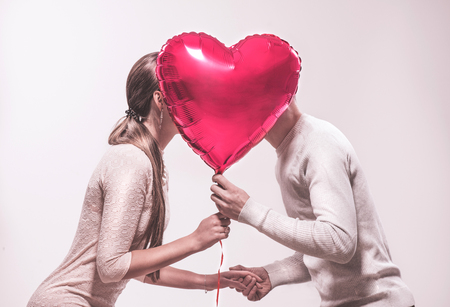 Photo pour Valentine's day. Happy joyful couple holding heart shaped air balloon and kissing. Love. Happy Valentine's Day celebrating - image libre de droit