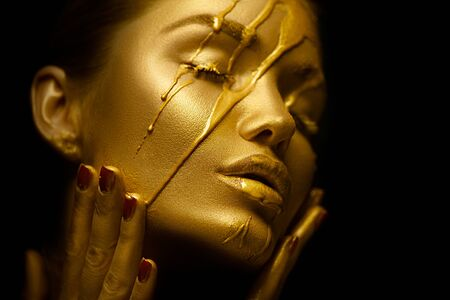 Photo pour Sexy beauty woman with golden metallic skin. Gold paint smudges drips from the face and sexy lips. Creative makeup - image libre de droit