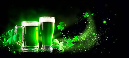 Photo for St. Patrick's Day Green Beer pint over dark green background, decorated with shamrock leaves. Patrick Day pub party, celebrating. Glass of Green beer close-up. Border art design, Wide format banner - Royalty Free Image