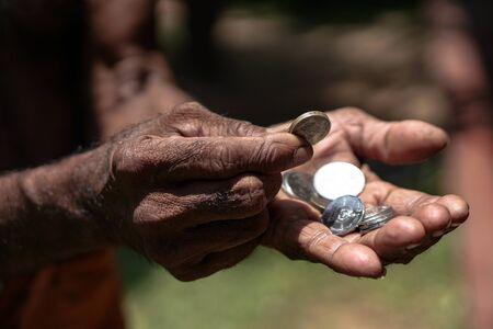 Foto de Coins in dark working hands. Beyond the poverty line in Asian countries. Subject soap bar. - Imagen libre de derechos