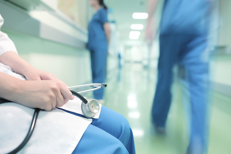 Photo for Doctor sitting alone in hospital corridor on the background of walking colleagues - Royalty Free Image