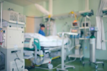 Foto de Critically ill patient surrounded by medical technologies in the ICU. Female doctor stands by patient bed working with equipment. Unfocused background. - Imagen libre de derechos