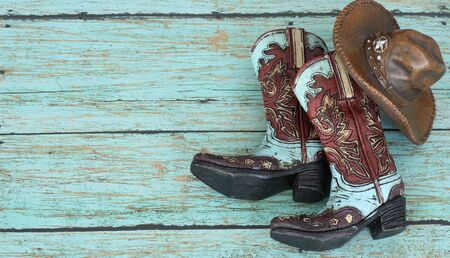 Photo pour teal and burnt red cowboy boots and hat on a teal wooden background with writing space - image libre de droit
