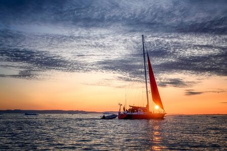 Foto de West Greenland Ilulissat Jakobshavn Jacobshaven sky sunset with red sailing boat - Imagen libre de derechos