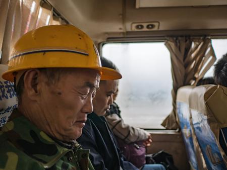 Foto per zhangjiajie/China - 14 October 2018: Unacquainted Chinese worker take a Bus to transit to wulingyuan From zhangjiajie City china.Zhangjiajie Huna China travel - Immagine Royalty Free
