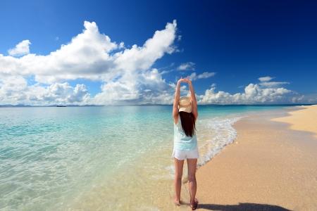 Photo pour young woman doing stretching exercises on beach - image libre de droit