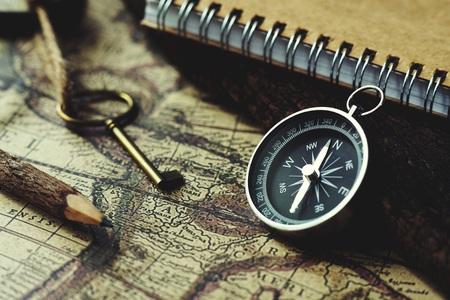 Photo pour Compass, key, pencil and book on blur vintage map background, retro classic color tone - image libre de droit