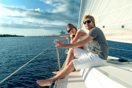 Photo pour Happy young couple relaxing on a yacht - image libre de droit