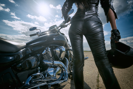 Foto de Biker girl in leather jacket standing by a motorcycle. Rear view - Imagen libre de derechos
