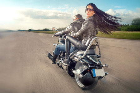 Foto de Biker Man and woman wearing black leather jackets and stylish sunglasses riding on motorcycle - Imagen libre de derechos