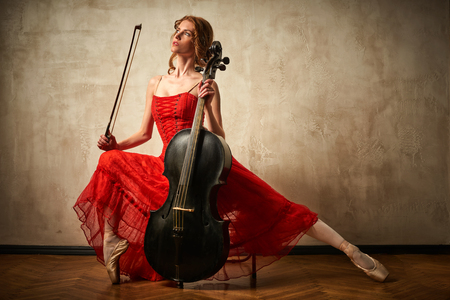 Photo for Female ballet dancer in red dress and pointe playing on antique black cello - Royalty Free Image