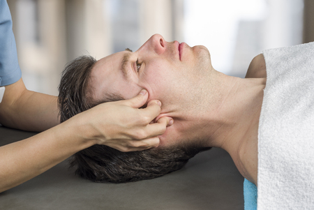 Photo for Physiotherapist, chiropractor doing a cranial sacral therapy to a man patient. Activating  trigeminal nerve. Osteopathy - Royalty Free Image