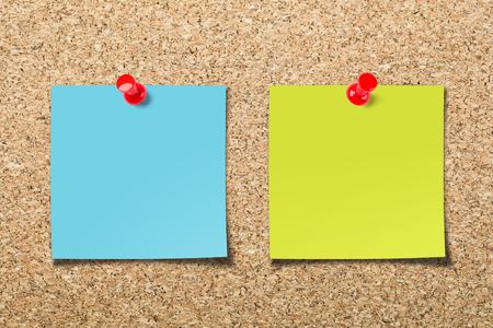 Foto de Cork board with two colorful blank sticky notes. - Imagen libre de derechos