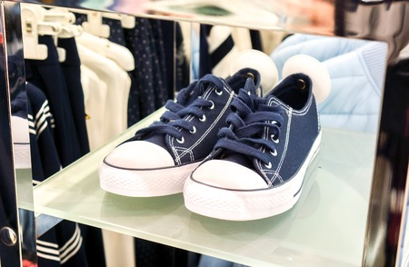 dark blue sneaker shoes wait for its master in sale season in big fashion shop. dark blue sport shoes with round white security magnet tag stay on white high shelf against modern clothes