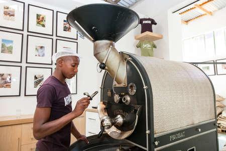 Foto de Johannesburg, South Africa - January 14, 2013: African Man operating a machine used to roast coffee beans - Imagen libre de derechos