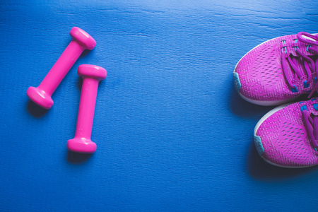 Fitness background, Equipment for gym and home dumbbell and Sneakers on color background. soft focus.