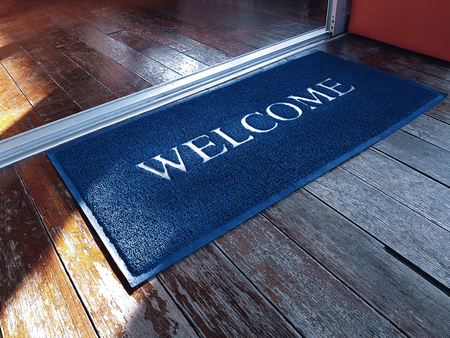 Foto per Blue Doormat with Welcome Text in Front of Shop - Immagine Royalty Free