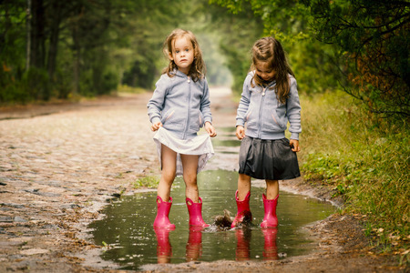 Foto de Two little girls walk by the puddle in a summer forest - Imagen libre de derechos