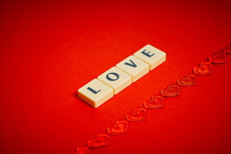 Photo for the love word arranged from blocks with letters on a beautiful red background - Royalty Free Image