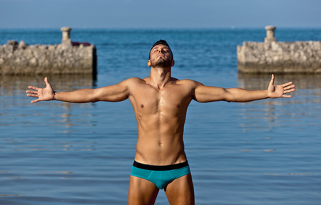 Photo for Young handsome muscular man in swimsuit on the stony beach. - Royalty Free Image
