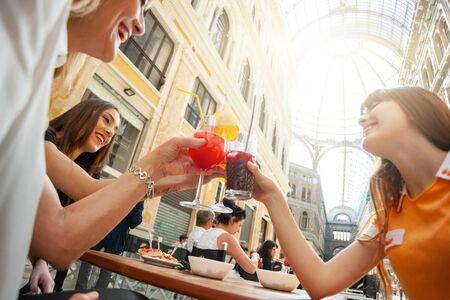 Foto de Friends do cheers with drinks in the gallery Umberto Primo in Naples. - Imagen libre de derechos