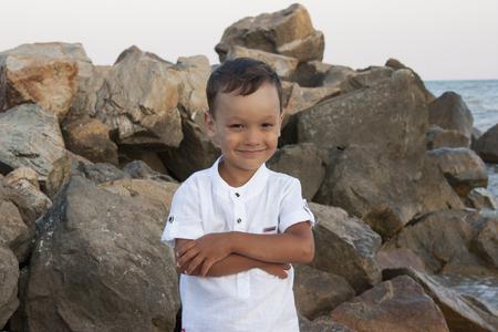 Foto de Boy child on sea stones smiles beautifully - Imagen libre de derechos