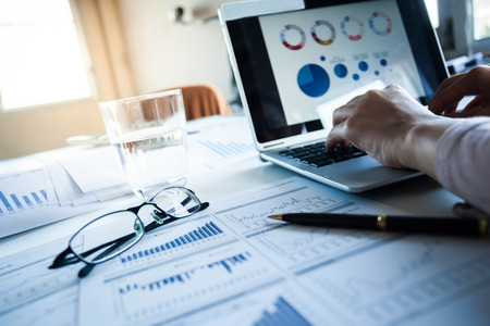Foto de Businessman checking reported profits on the paper and laptop. - Imagen libre de derechos