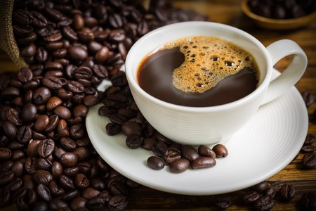 Photo for Coffee Cup and Beans on Wooden Table - Royalty Free Image