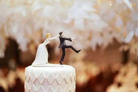Foto de groom doll and statue is running away but bride can catch him finally. the funny wedding story doll on the top of cake. - Imagen libre de derechos